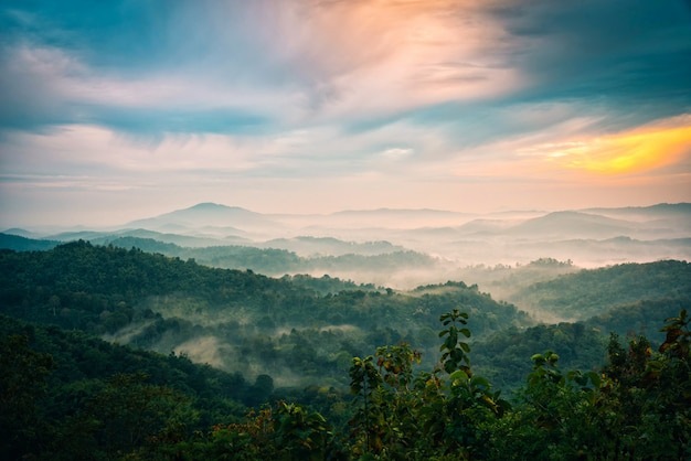 Foggy in montagna con cielo drammatico al sorgere del sole