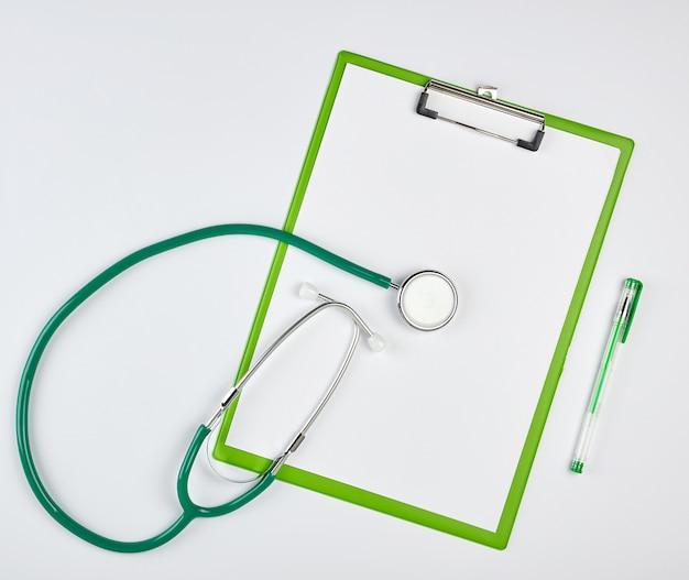 Fogli bianchi vuoti e stetoscopio medico verde su sfondo bianco