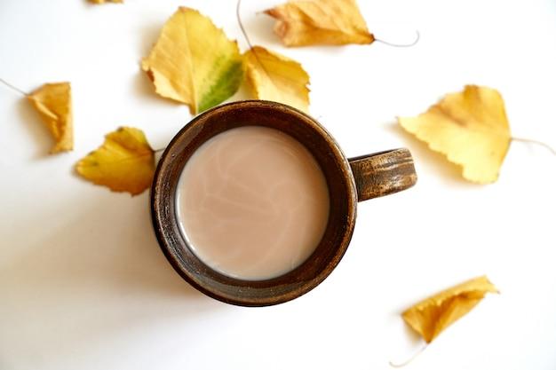 Fogli di autunno con caffè o la tazza di tè su bianco
