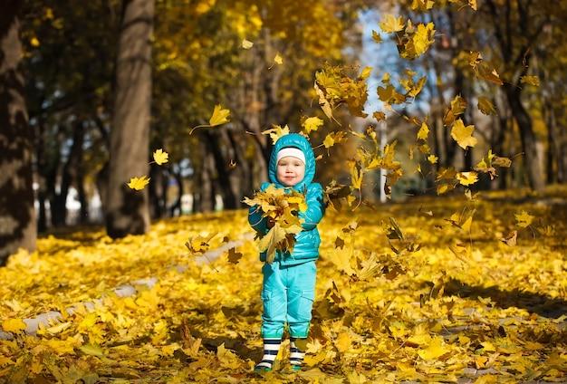 Fogli di autunno di lancio della bambina