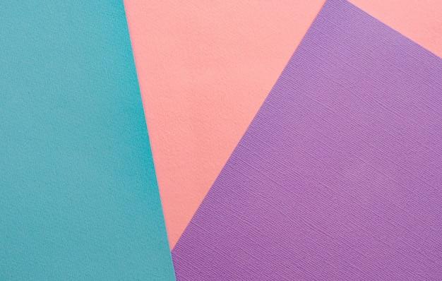 Fogli di carta colorata sullo sfondo. rosa, turchese, viola.