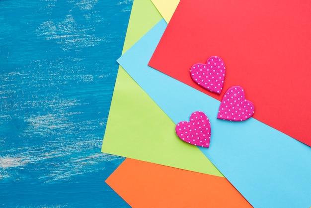 Fogli di carta colorati su un cuore decorativo del fondo blu dipinto di legno