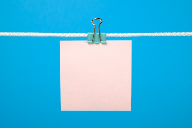 Fogli di carta rosa in bianco che appendono sulla corda