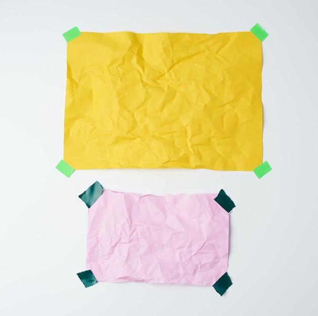 Fogli di carta sgualciti gialli e rosa vuoti incollati con pezzi appiccicosi verdi