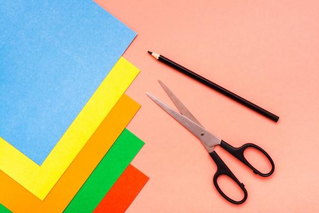 Fogli di cartone colorato, forbici e matita su rosso