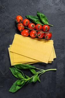 Fogli di lasagne crude. ingredienti basilico, pomodorini. sfondo nero. vista dall'alto. spazio per il testo