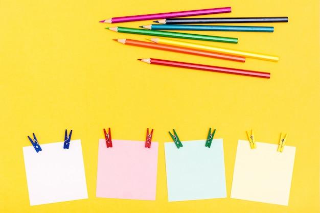 Fogli per la scrittura di spille appuntate e matite colorate su uno sfondo giallo