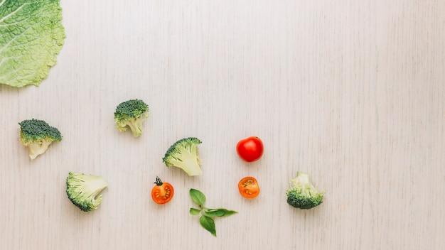 Foglia di cavolo; broccoli; basilico e pomodorini su superficie di legno
