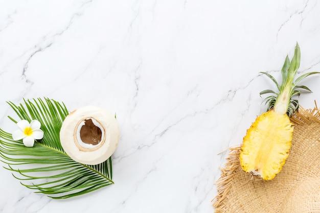 Foglia di palma tropicale, grande cappello di paglia, cocco, ananas su marmo bianco