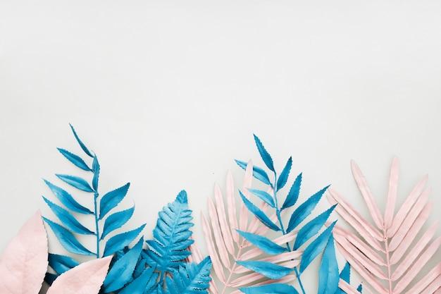 Foglia di palma tropicale rosa e blu nel colore audace vibrante su fondo bianco.