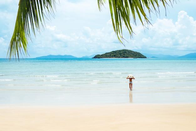 Foglia verde della palma e giovane donna che stanno mare vicino