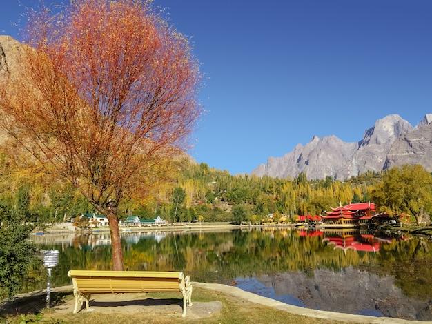 Fogliame colorato in autunno con riflesso nell'acqua di alberi e montagne.
