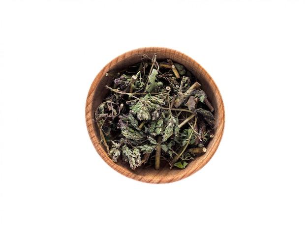 Foglie asciutte dell'origanum vulgare in una tazza di legno su un bianco