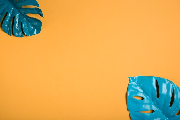 Foglie blu su sfondo arancione con spazio di copia
