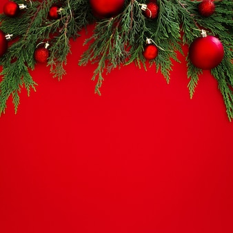 Foglie del pino di natale decorate con le palle rosse su fondo rosso con copyspace