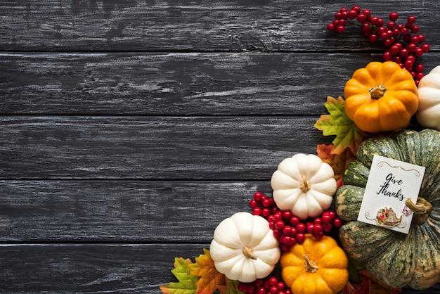 Foglie di acero di autunno con la zucca e le bacche rosse su vecchio fondo di legno. ringraziamento