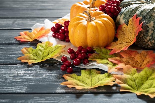 Foglie di acero di autunno con la zucca e le bacche rosse su vecchio fondo di legno.