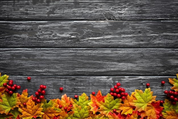 Foglie di acero di autunno con le bacche rosse su vecchio fondo di legno. concetto del giorno del ringraziamento.