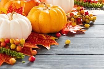 Foglie di acero e zucca di autunno su vecchio fondo di legno. Concetto del giorno del ringraziamento.