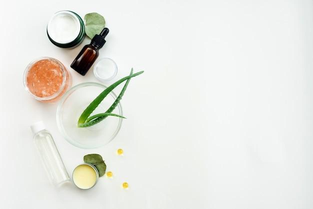 Foglie di aloe crema idratante, maschera e tonico su un tavolo bianco. creazione di prodotti di bellezza naturali a casa. miscelazione di estratti naturali per la produzione di siero antietà