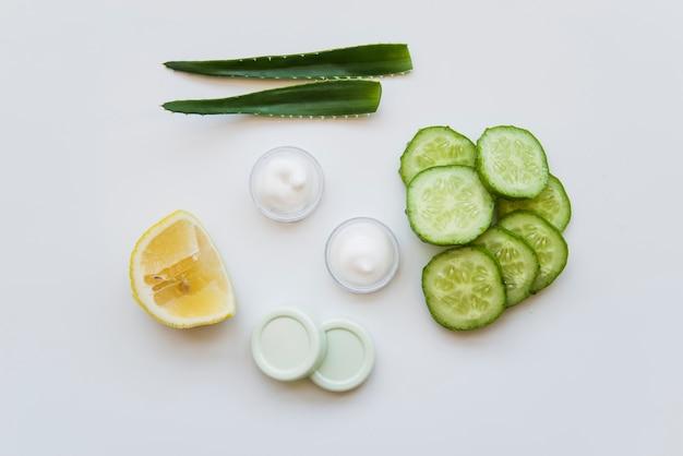 Foglie di aloe vera; crema idratante; fette di limone e cetriolo su sfondo bianco