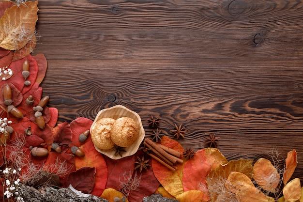 Foglie di autunno, biscotti e cannella su legno