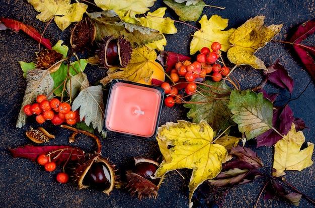 Foglie di autunno, castagne, candele su un buio