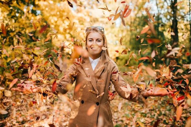 Foglie di autunno di lancio sorridenti di giovane signora su in parco soleggiato