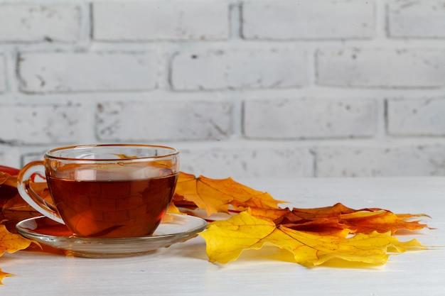 Foglie di autunno e tazza di cottura a vapore calda di tè su superficie di legno
