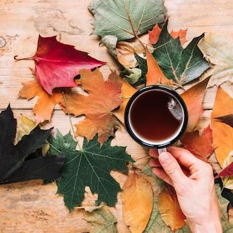 Foglie di autunno e tazza di tè su fondo di legno
