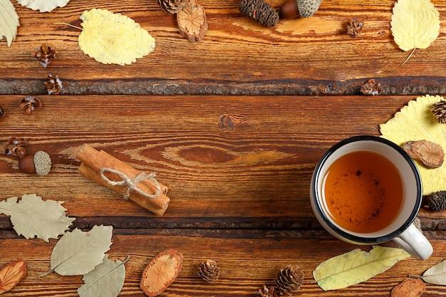 Foglie di autunno gialle e un bicchiere di tè su un vecchio fondo di legno scuro con uno spazio in bianco per testo
