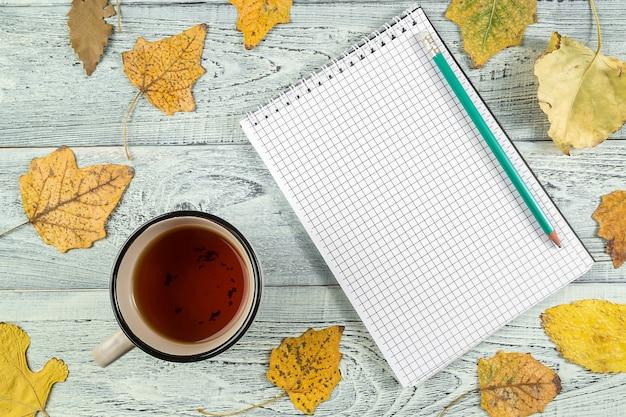 Foglie di autunno gialle, una tazza di tè e un taccuino su un fondo di legno vecchio leggero