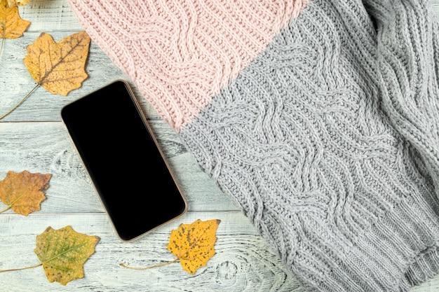 Foglie di autunno gialle, una tazza di tè e uno smartphone su un vecchio fondo di legno