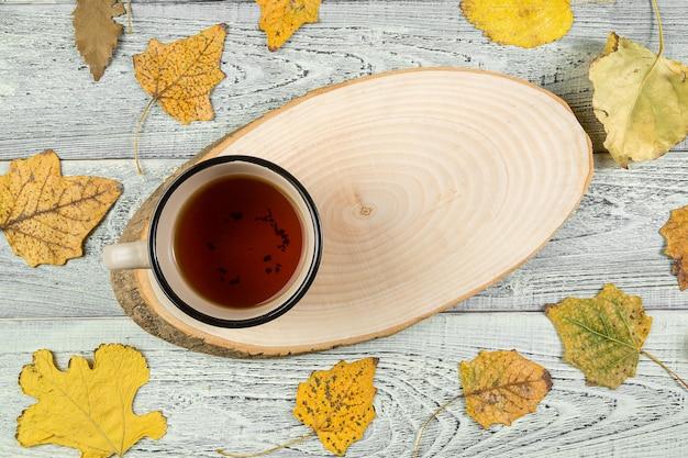 Foglie di autunno gialle, una tazza di tè su un vecchio fondo di legno