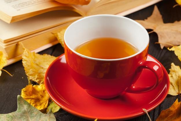 Foglie di autunno, libro e tazza di tè