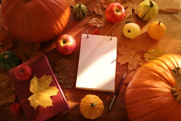 Foglie di autunno, quaderno, mele e zucche