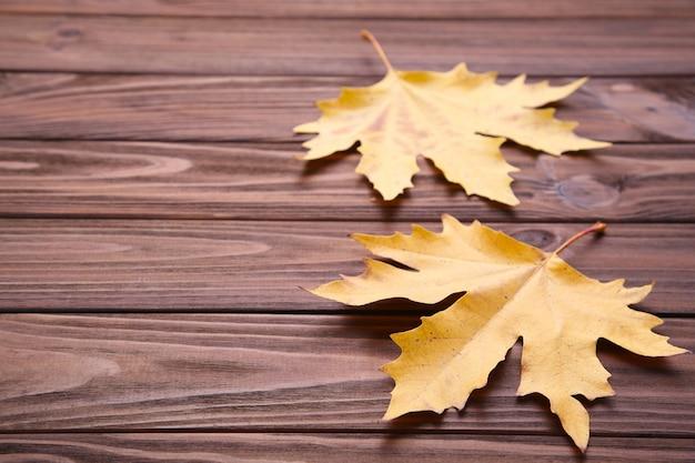 Foglie di autunno rosse ed arancio sulla tavola marrone