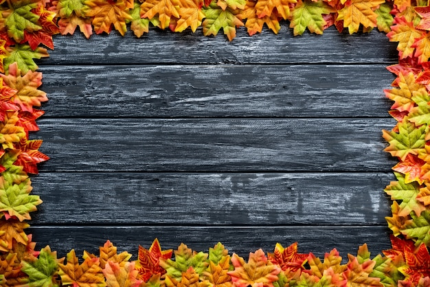 Foglie di autunno su un fondo di tavolo in legno nero. ringraziamento, concetto di halloween