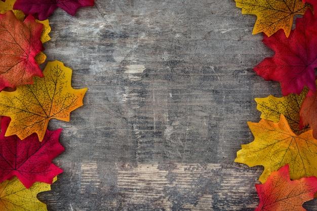 Foglie di autunno sul fondo della struttura di legno