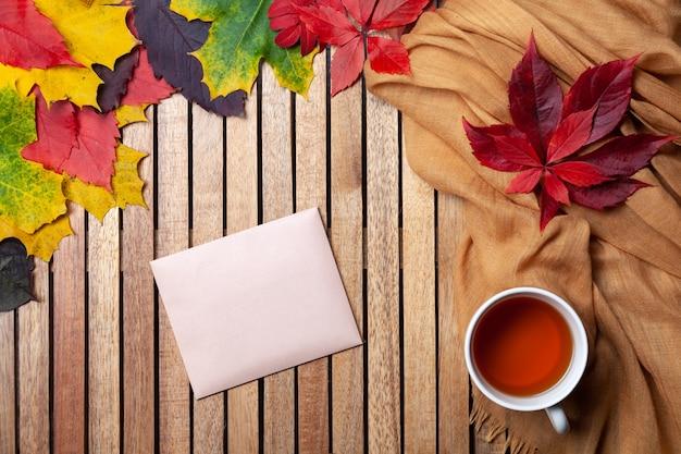 Foglie di autunno, tazza di tè bianco sul tavolo, tovagliolo tessile, fondo in legno
