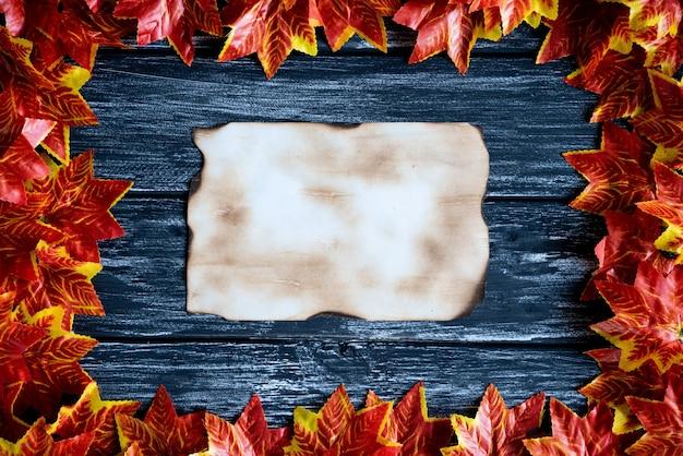 Foglie di autunno variopinte e vecchia carta su un fondo di tavolo in legno nero. ringraziamento, hal