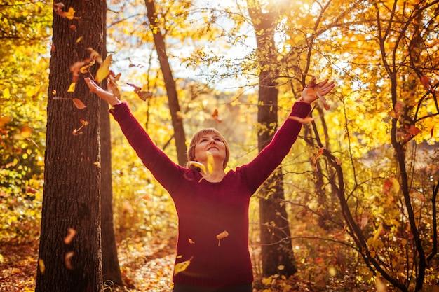 Foglie di lancio della donna di mezza età nella foresta
