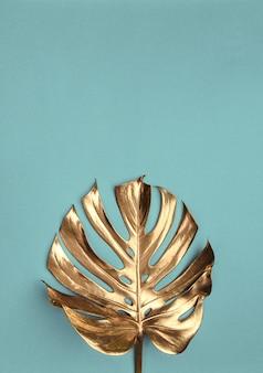 Foglie di monstera d'oro su sfondo turchese chiaro