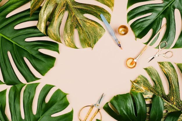 Foglie di monstera dipinte d'oro con vari accessori fissi: pennelli, forbici, vernice su fondo pastello