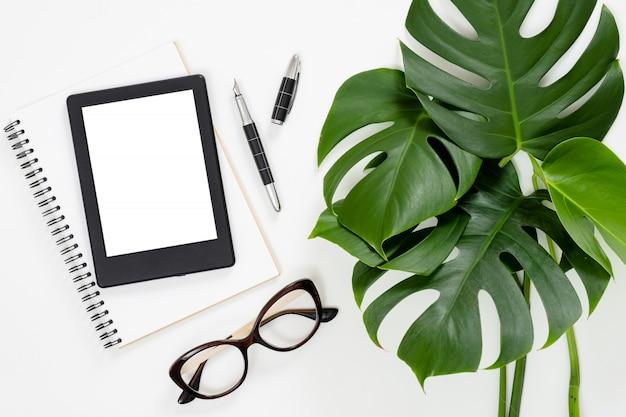 Foglie di monstera tropicali distese piatte, quaderno di carta, lettore di e-book, occhiali