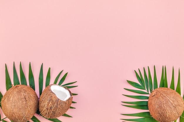 Foglie di palma e noci di cocco sul tavolo rosa