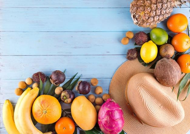 Foglie di palma tropicali, cappello, molti frutti su fondo di legno blu.