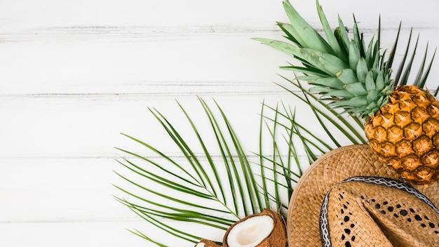 Foglie di piante vicino a frutti tropicali e cappello