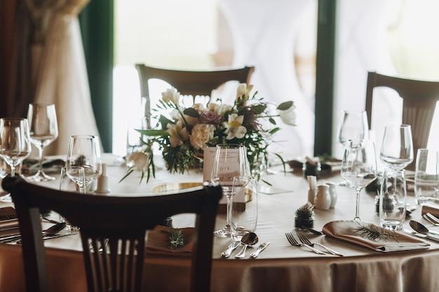 Foglie di pino e bouquet sul tavolo decorato di classe