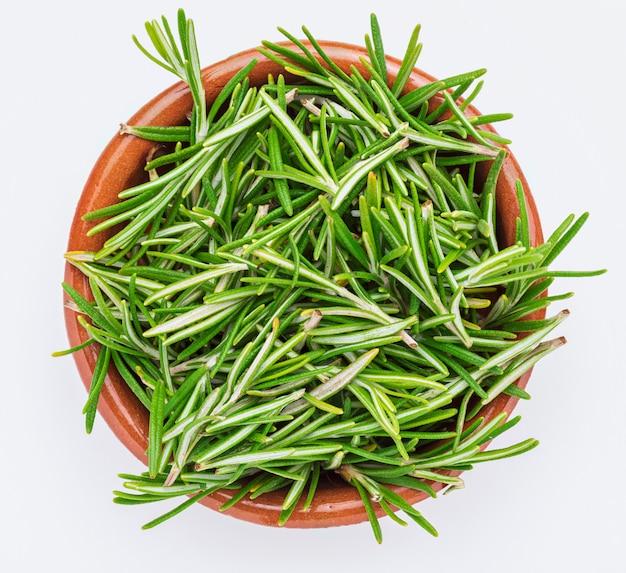 Foglie di rosmarino verde appena tagliate (rosmarinus officinalis) in una ciotola di argilla. aspetto rustico ingrediente isolato di cucina mediterranea e rimedio casalingo curativo.